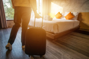 woman pulling her luggage into a hotel room