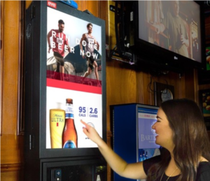 woman interacting with a digital advertisement in a bar