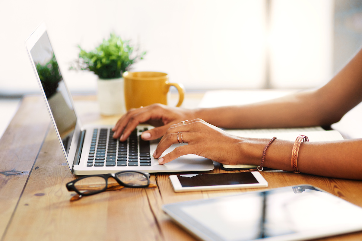 close up of woman's hands and arms using a laptop working from home