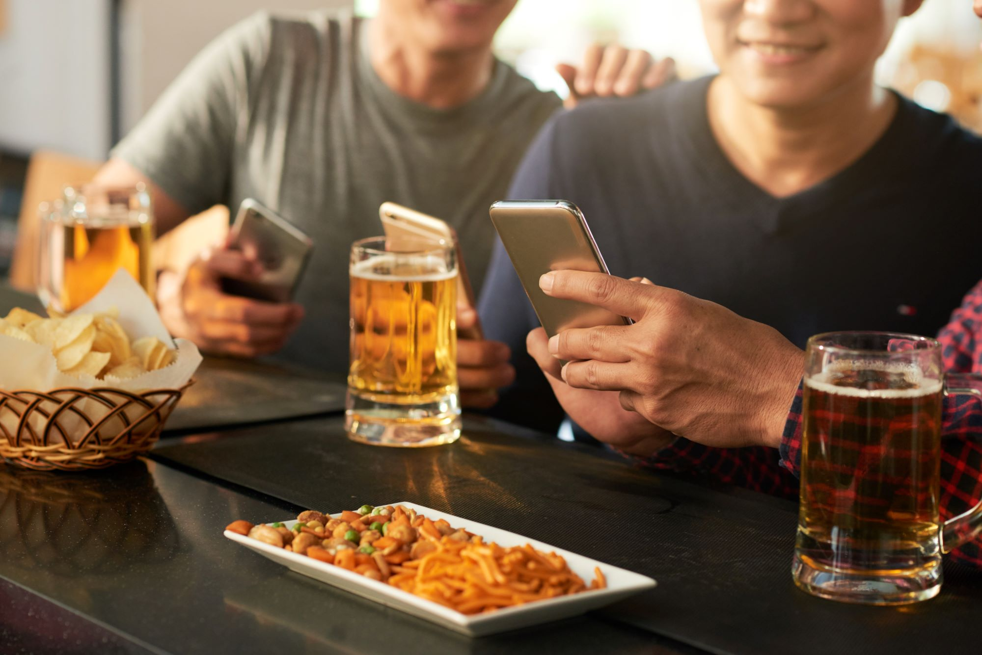 friends gathered at a bar with appetizers