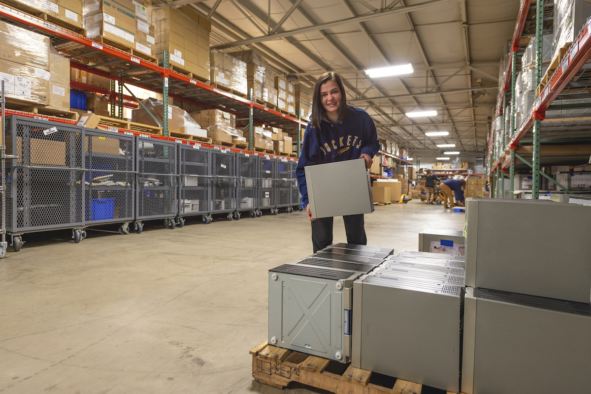 Young happy girl holding a box standing next to a pallet of boxes in a warehouse