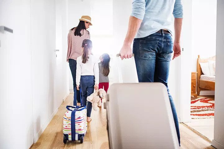 Family of four walking out of their home with suitcases